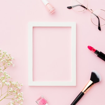 Pincel de maquillaje y lápiz labial con marco vacío
