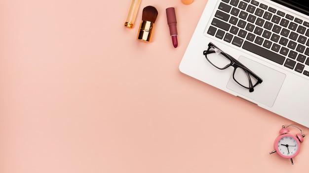 Pincel de maquillaje, lápiz de labios cerca de la computadora portátil con lentes y reloj despertador sobre fondo de color