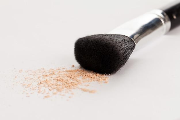 Pincel de maquillaje natural con polvo beige