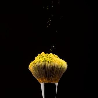 Pincel de maquillaje negro con polvo amarillo.