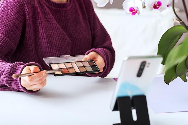 Pincel de maquillaje y paleta de sombras de ojos en blogger de belleza manos femeninas. el artista de maquillaje realiza grabaciones de contenido de video en línea, revisión de transmisión en vivo sobre productos cosméticos. entrenamiento de visagiste, creador de contenido