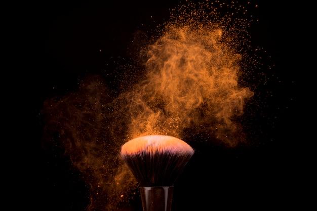 Pincel de maquillaje con partículas voladoras de polvo ligero.