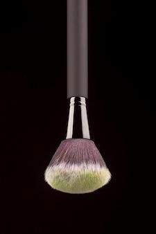 Pincel de maquillaje profesional con polvo amarillo sobre fondo negro