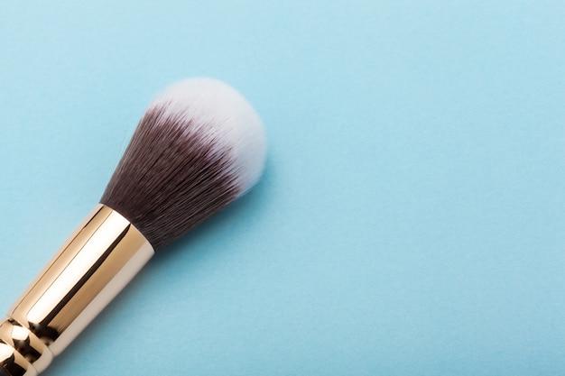 Pincel de maquillaje profesional sobre fondo azul.