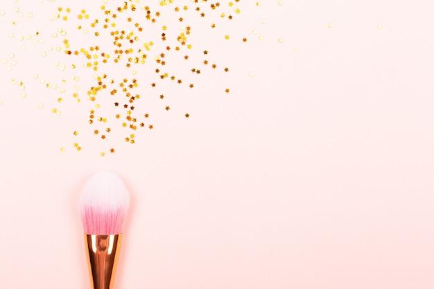 Pincel de maquillaje rosa y confeti