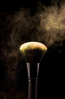 Pincel de maquillaje con salpicaduras de polvo amarillo