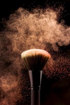 Pincel de maquillaje con salpicaduras de polvo color melocotón