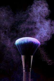 Pincel de maquillaje con salpicaduras de polvo púrpura
