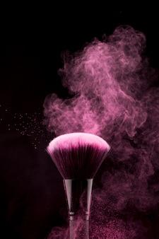 Pincel de maquillaje con salpicaduras de polvo rosa parpadeante