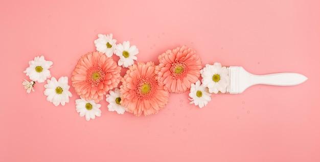 Pincel con margaritas y flores de gerbera