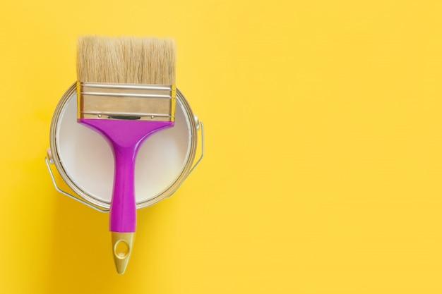 Pincel morado con lata abierta de pintura blanca sobre amarillo,