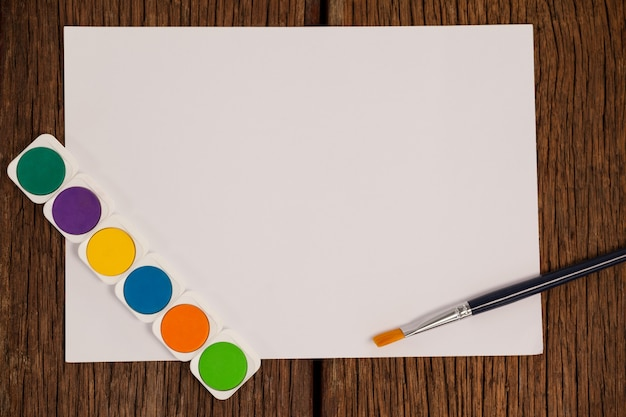 Pincel, paleta de acuarela y papel blanco sobre fondo blanco.
