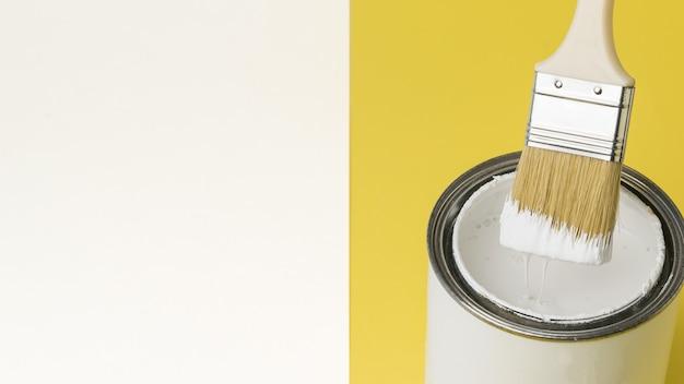 Pincel con pintura blanca goteando sobre un frasco sobre un fondo blanco y amarillo. ejecución de trabajos de pintura. lugar para el texto.