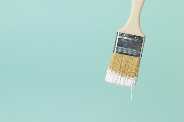 Pincel con pintura blanca que gotea sobre un fondo azul. ejecución de trabajos de pintura.