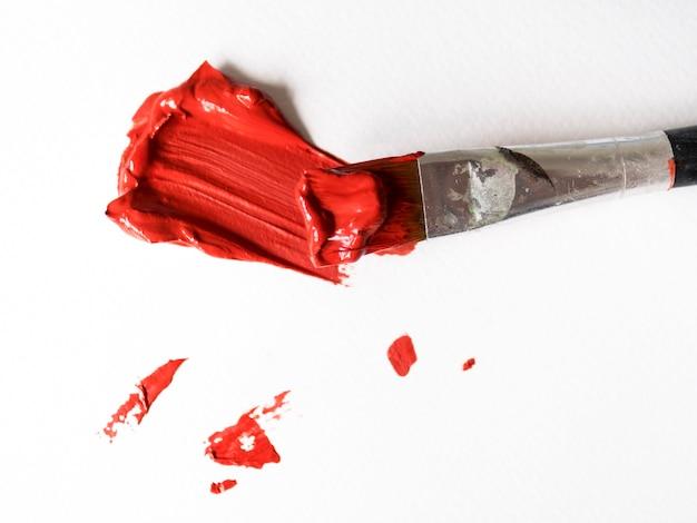 Pincel con pintura roja sobre lienzo.
