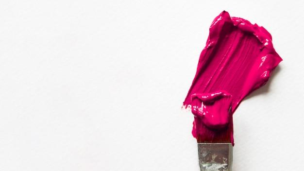 Pincel con pintura rosa sobre lienzo blanco.