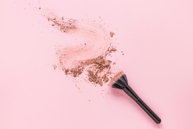 Pincel en polvo con polvo desmenuzado esparcido sobre la mesa