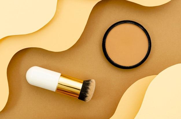 Pincel y polvo sobre fondo beige