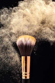 Pincel profesional de maquillaje negro con polvo