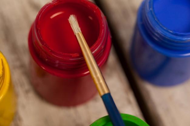 Pincel sobre pinturas de acuarela sobre mesa de madera