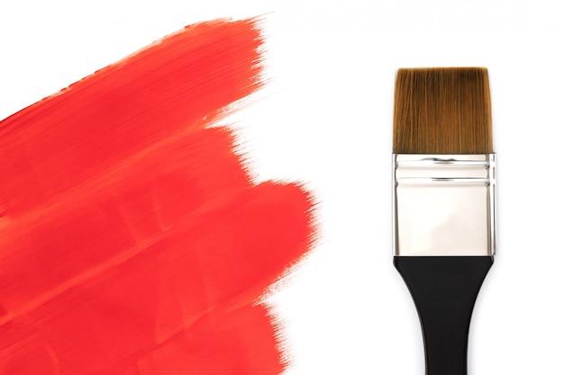Pincel y trazos de pintura roja. aislado sobre fondo blanco