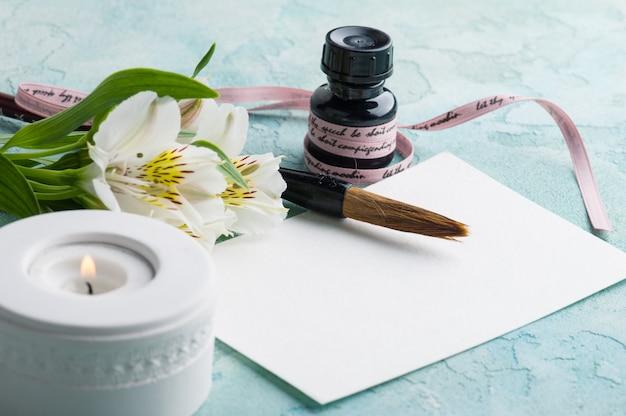 Pincel con velas encendidas, papel y flores.