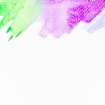Pincelada de acuarela verde y púrpura sobre fondo blanco