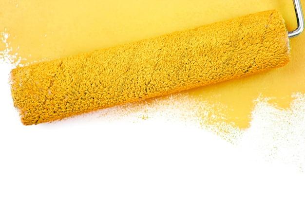 Pincelada amarilla y un rodillo de pintura