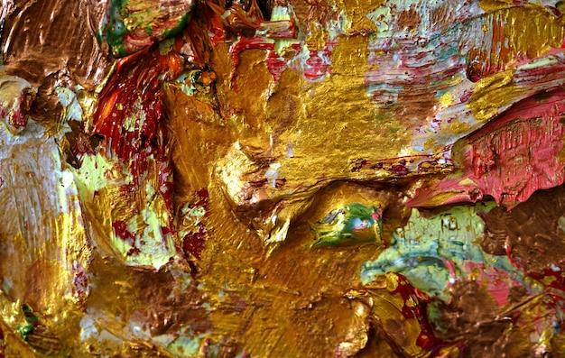 Pincelada de pintura al óleo de oro colorido sobre lienzo de fondo abstracto con textura.