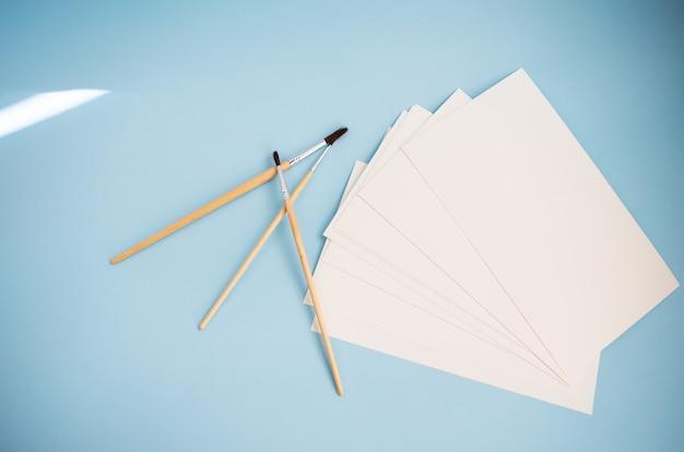 Pinceles de acuarela de diferentes tamaños se encuentran junto con papel de acuarela sobre un fondo azul. lecciones de dibujo.