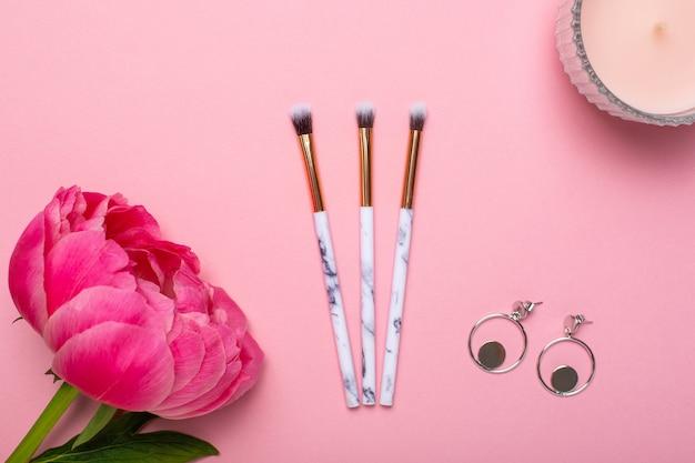 Pinceles y aretes de maquillaje para mujer con una hermosa flor de peonía