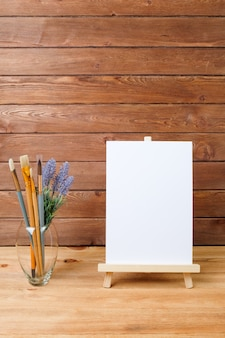 Pinceles de arte y caballete sobre fondo de madera