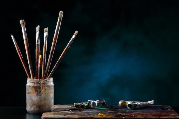 Pinceles de artista y una paleta con pinturas sobre fondo azul.