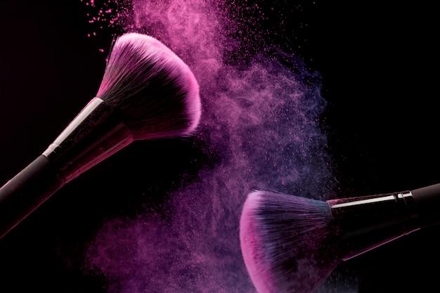 Pinceles cosméticos y polvo de maquillaje sobre fondo oscuro