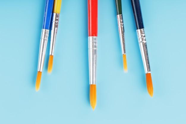 Pinceles de diferentes colores para dibujar, creatividad y arte sobre un fondo azul.