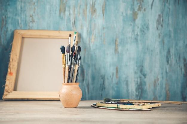 Pinceles en el escritorio sobre fondo abstracto