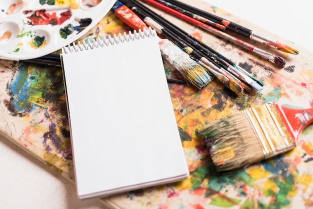 Pinceles manchados con cuaderno