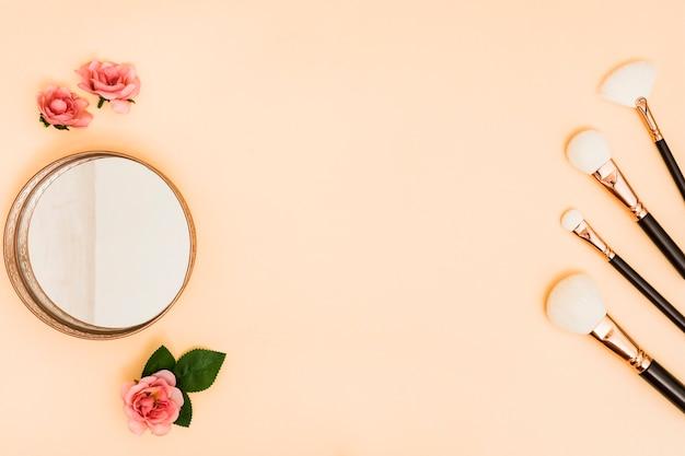 Pinceles de maquillaje blanco con polvo compacto y rosas sobre fondo coloreado