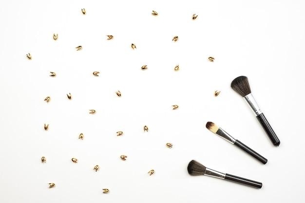 Pinceles de maquillaje cosmético y baratijas doradas sobre blanco