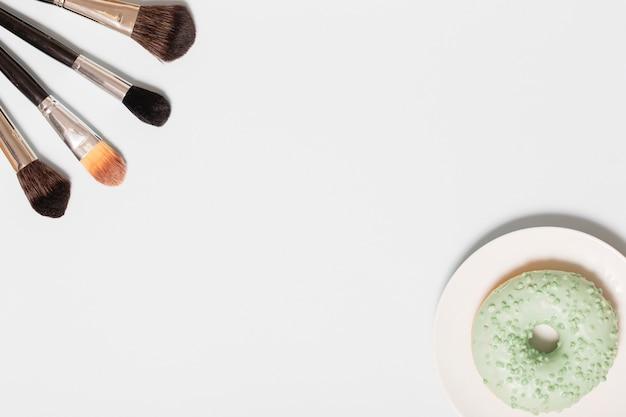 Pinceles de maquillaje y donut verde