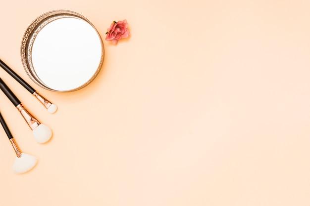 Pinceles de maquillaje; espejo circular y rosa sobre fondo beige.