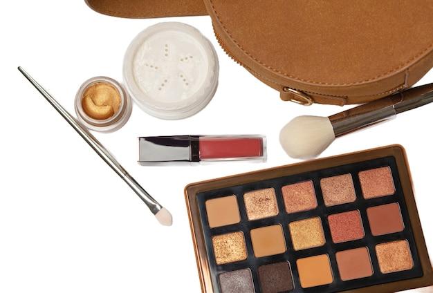 Los pinceles de maquillaje, el lápiz labial y la paleta de sombras de ojos se caen del bolso. fondo blanco