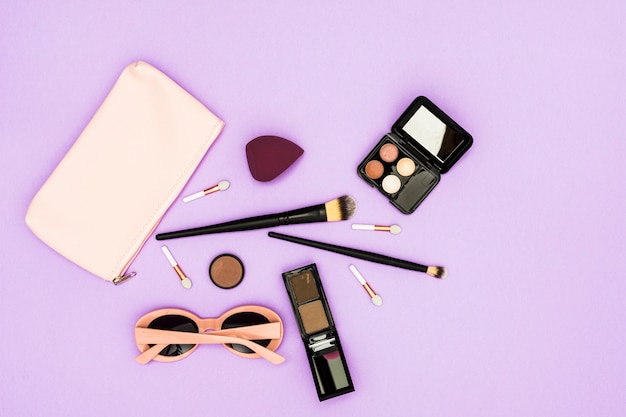 Pinceles de maquillaje; paleta de sombra de ojos y gafas de sol sobre fondo púrpura