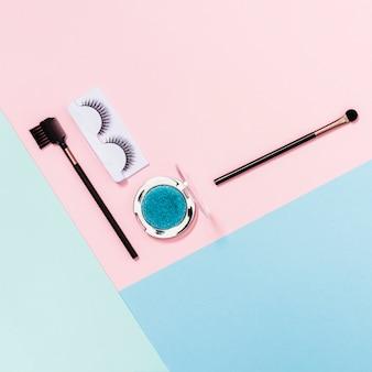 Pinceles de maquillaje; pestañas y sombras de ojos azules en rosa; telón de fondo azul y verde claro