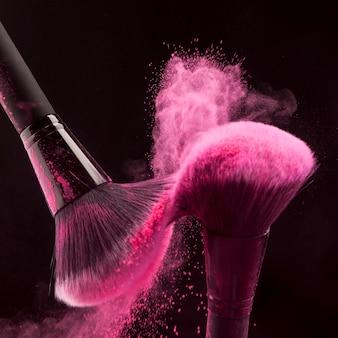 Pinceles de maquillaje con polvo rosa haze