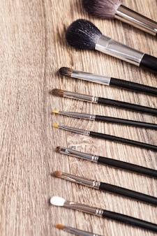Pinceles de maquillaje profesional sobre fondo de madera. industria de la belleza