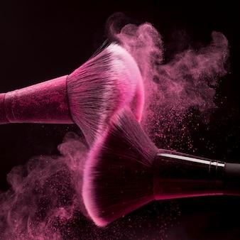 Pinceles de maquillaje con salpicaduras de polvo rosa