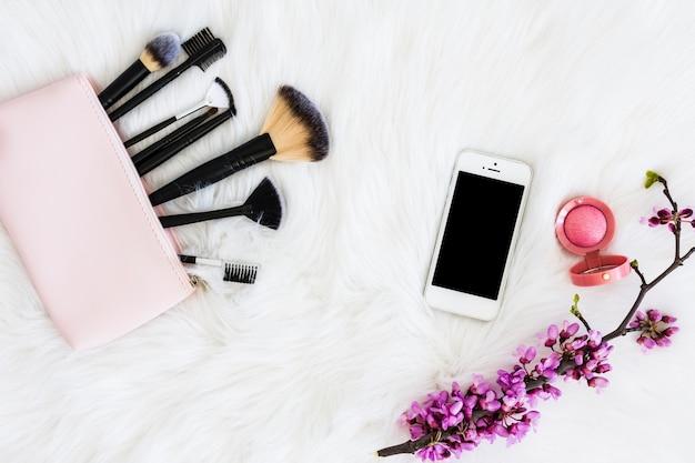 Pinceles de maquillaje con smartphone; polvo facial compacto y ramita de flores en piel blanca.