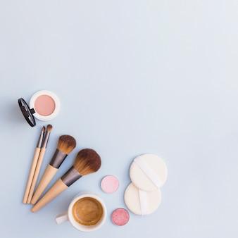 Pinceles de maquillaje; sombra; colorete y esponja con taza de café sobre fondo azul