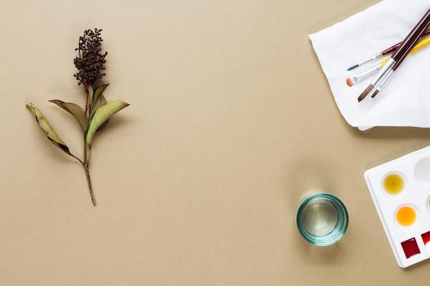 Pinceles con paleta de acuarela y flor.